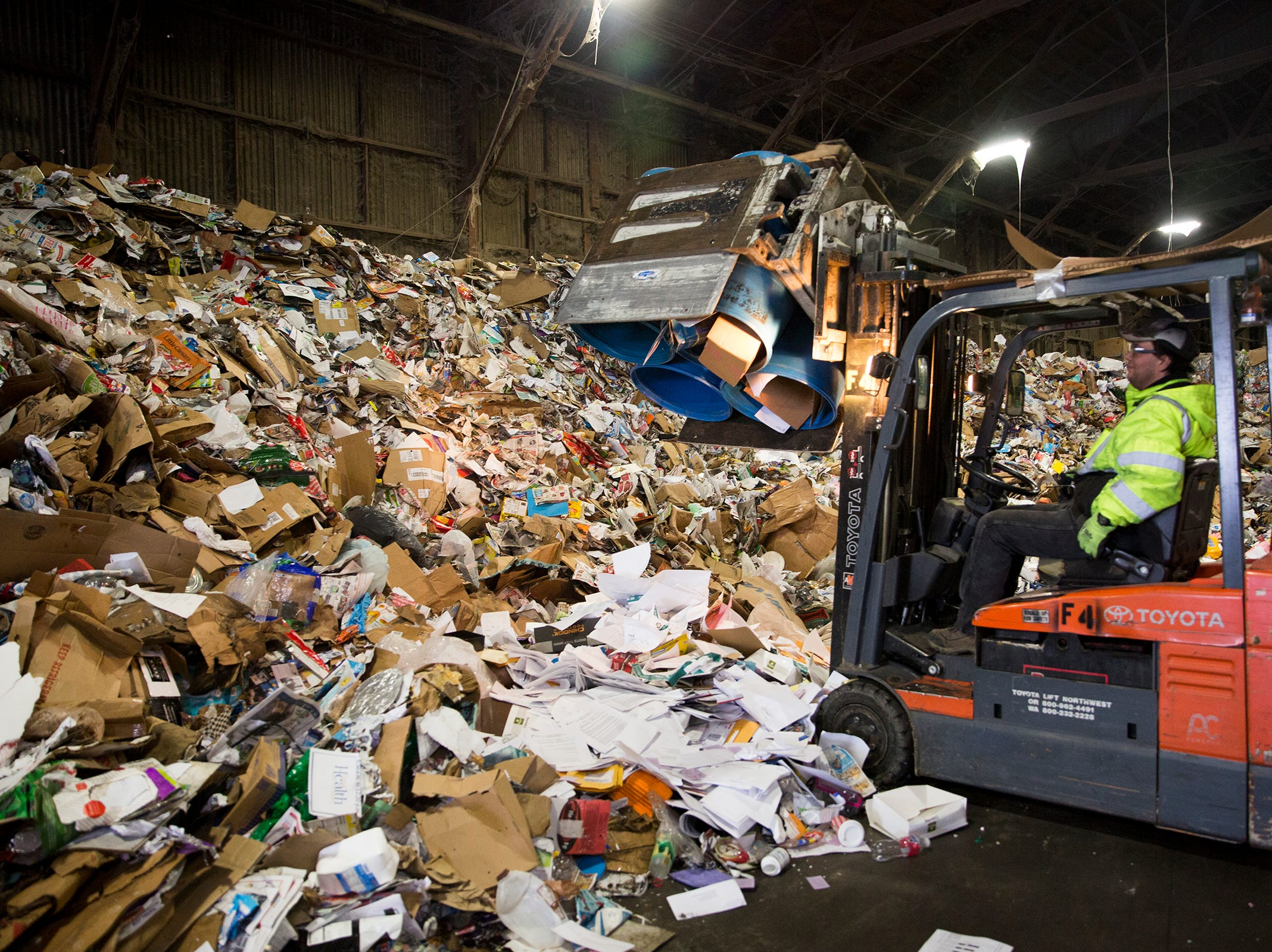 Garten Recycling employee Jody Ulricksen uses a forklift to pick up recycled items before they are sorted in Salem on Thursday, Dec. 20, 2018.