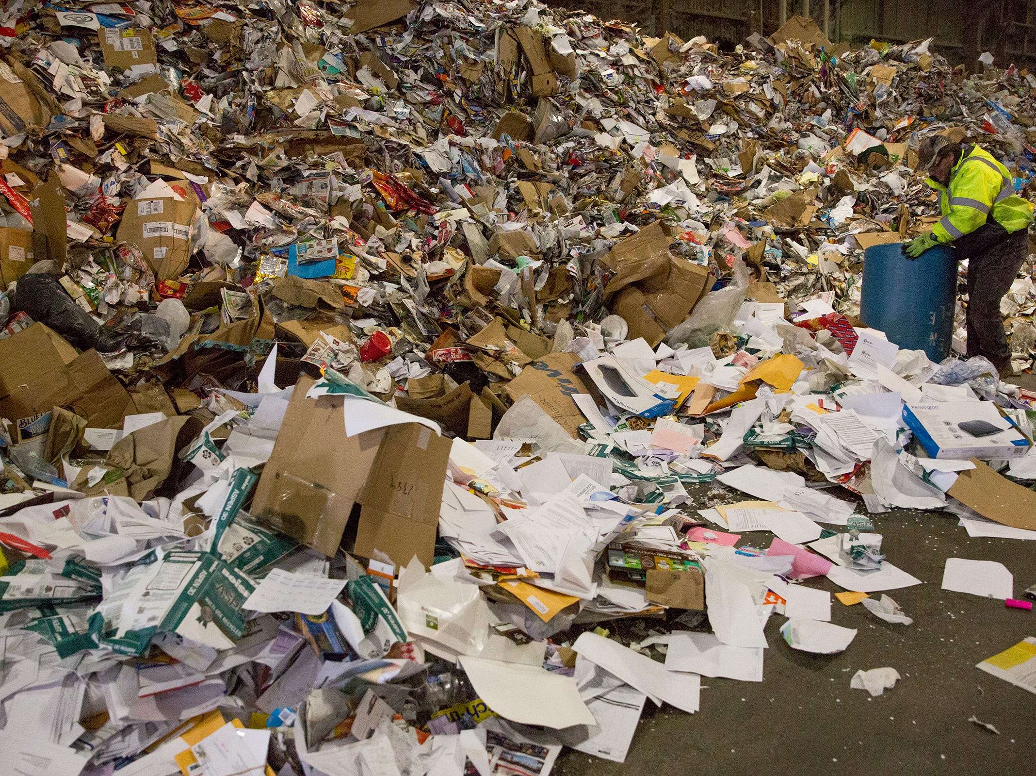 Garten Recycling employee Jody Ulricksen sorts through paper and other recycled items before they are separated in Salem on Thursday, Dec. 20, 2018.