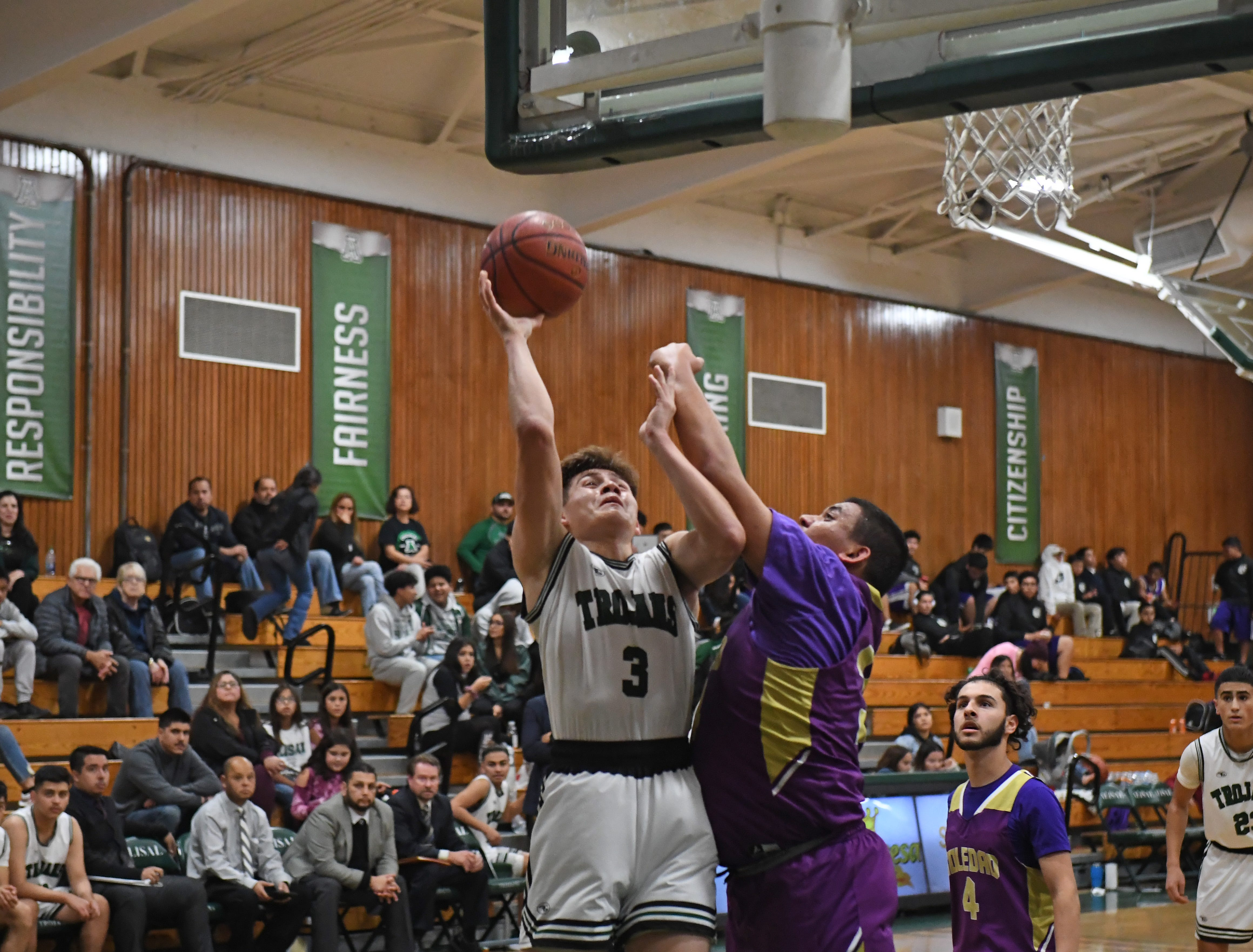 Alisal forward Ronaldo Enriquez (3) puts up a shot while taking contact from the defense.