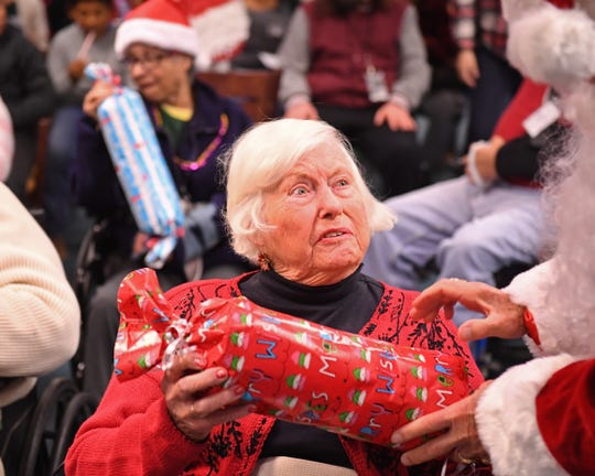 Marilyn Olsen, 85, a Pebble Beach resident, receives a wrapped gift after participating in the Christmas carols.