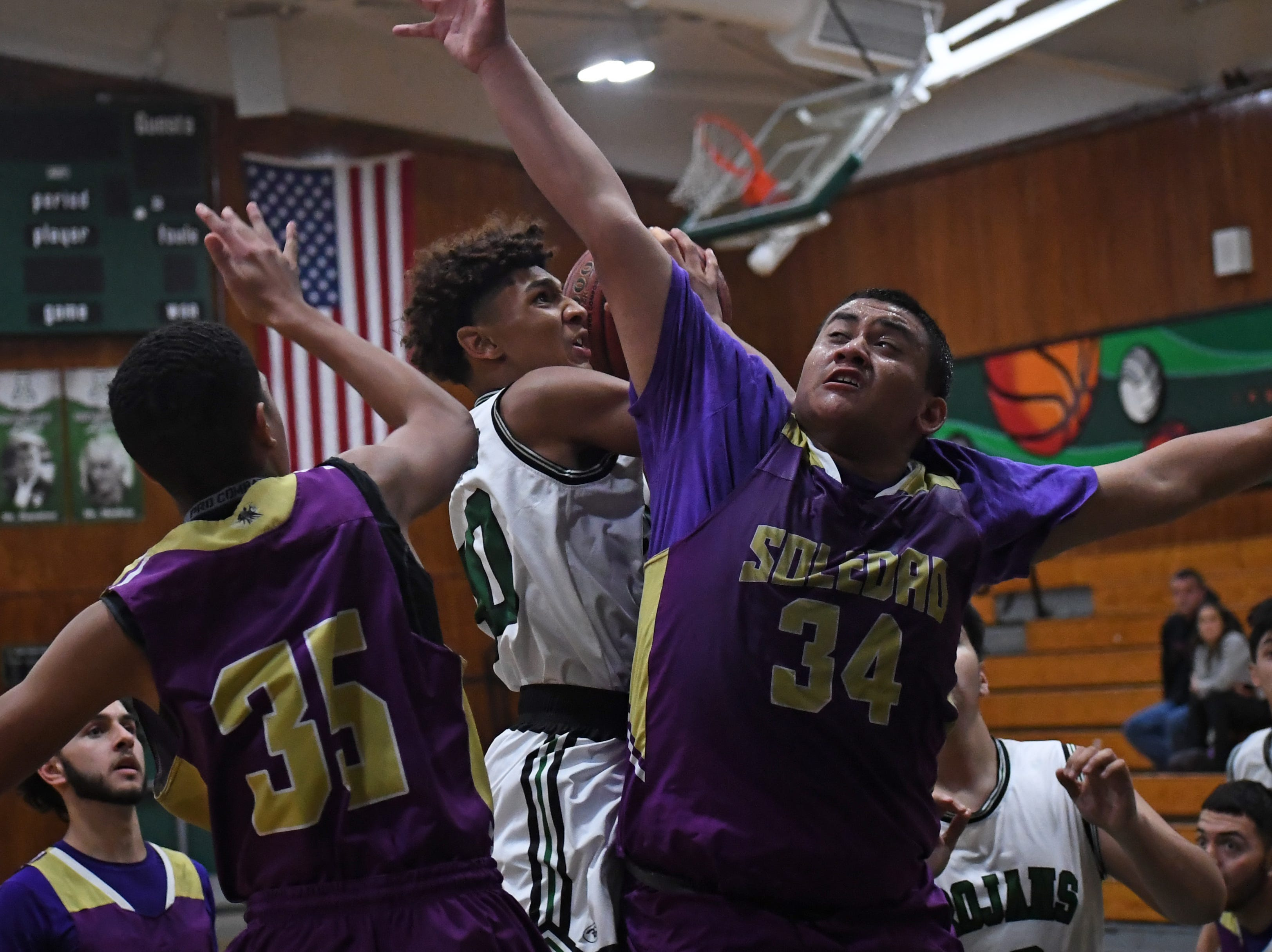 Alisal guard Izahias Carrillo (20) puts up a shot while absorbing contact.
