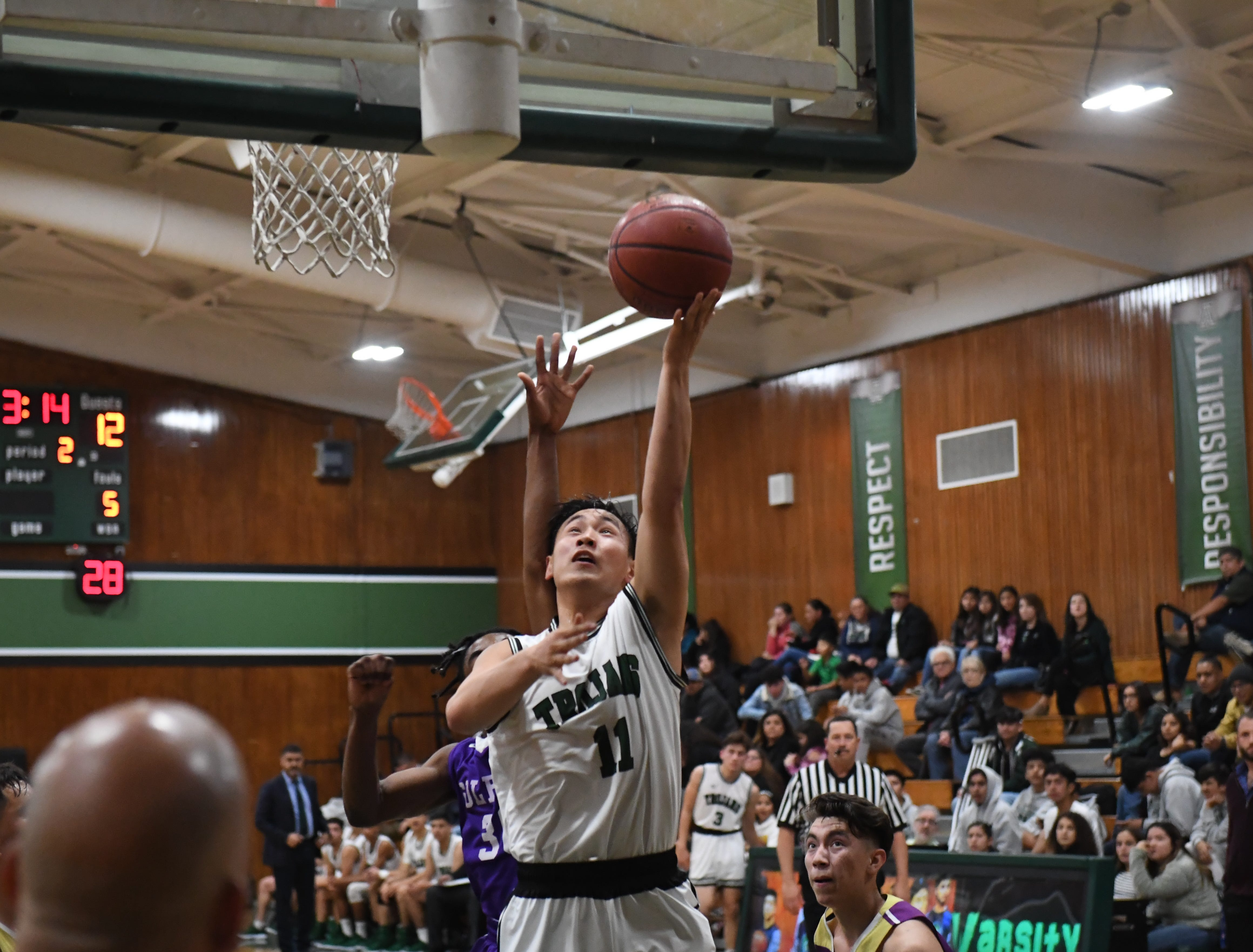 Alisal guard Joshua Vuoung (11) puts up a layup despite the contact from a Soledad defender.