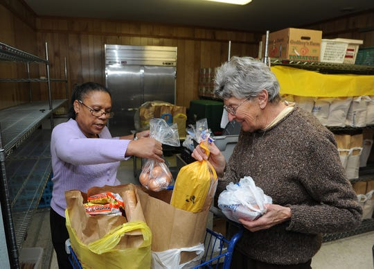 Sister Eileen Eager, right, seen in this file image packing food for a client at the Seton Center pantry, is leaving the program she founded in 1983 with three other nuns.