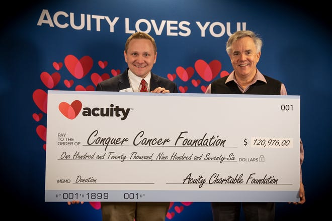 Acuity President and CEO Ben Salzmann (right) presents a check to Dave Wiemer, Philanthropic Officer at Conquer Cancer Foundation. Conquer Cancer Foundation received over $120,000 from Acuity, while five other charities received a total of nearly $380,000.