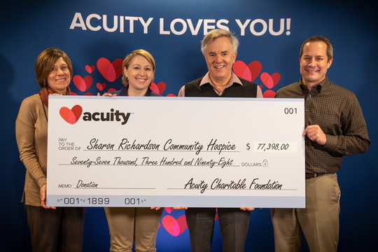 Charmaine Conrad, Director of Development and Communications (far left), and volunteer Deanne Perez from Sharon S. Richardson Community Hospice accept a check for over $77,000 from Acuity President and CEO Ben Salzmann (left) and Shane Paltzer, Vice President - Personal Lines and Marketing.