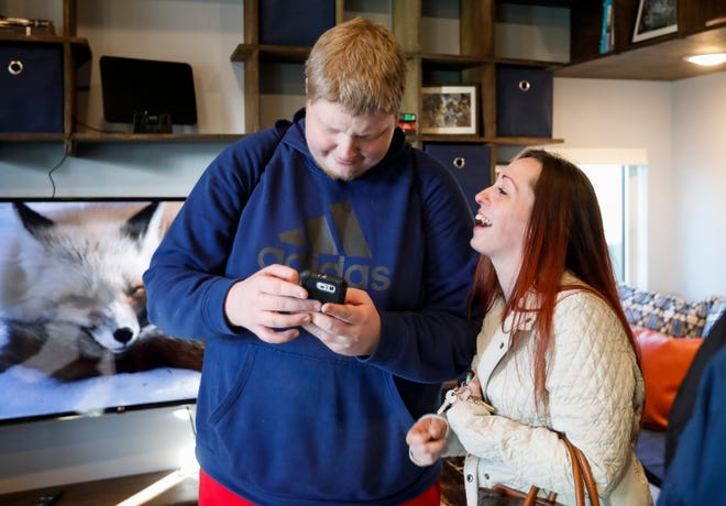 M.J. and his friend Mandy Fenner laugh while looking at photos on her phone inside his new home at Eden Village on Friday, Dec. 21, 2018.