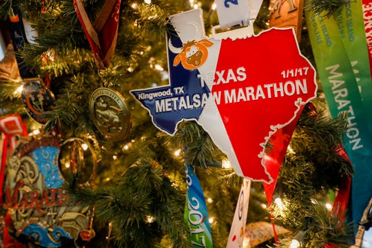 Calix Fattmann and his father, Ken Fattmann, decorated their Christmas tree with all of Calix's marathon medals. Calix, who is 17, is on track to be the youngest person to run 100 marathons.