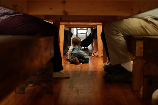 While the rest of his family eats their Thanksgiving meal, Jayant Karnik crawls around under the two tables that span across the dining room at the home of his maternal grandmother in Monticello, Fla. Thursday, Nov. 22, 2018.