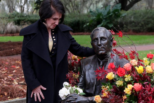 Ginger Wetherell takes a moment with the statue of her husband Florida State University President Emeritus T.K. Wetherell that is covered in flowers just moments after a funeral service for Wetherell held at Ruby Diamond Concert Hall Friday, Dec. 21, 2018.