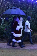 Santa makes his way through the rain to meet children and hear their Christmas lists at Elf Night at Dorothy B. Oven Park, Thursday, Dec. 21, 2018.