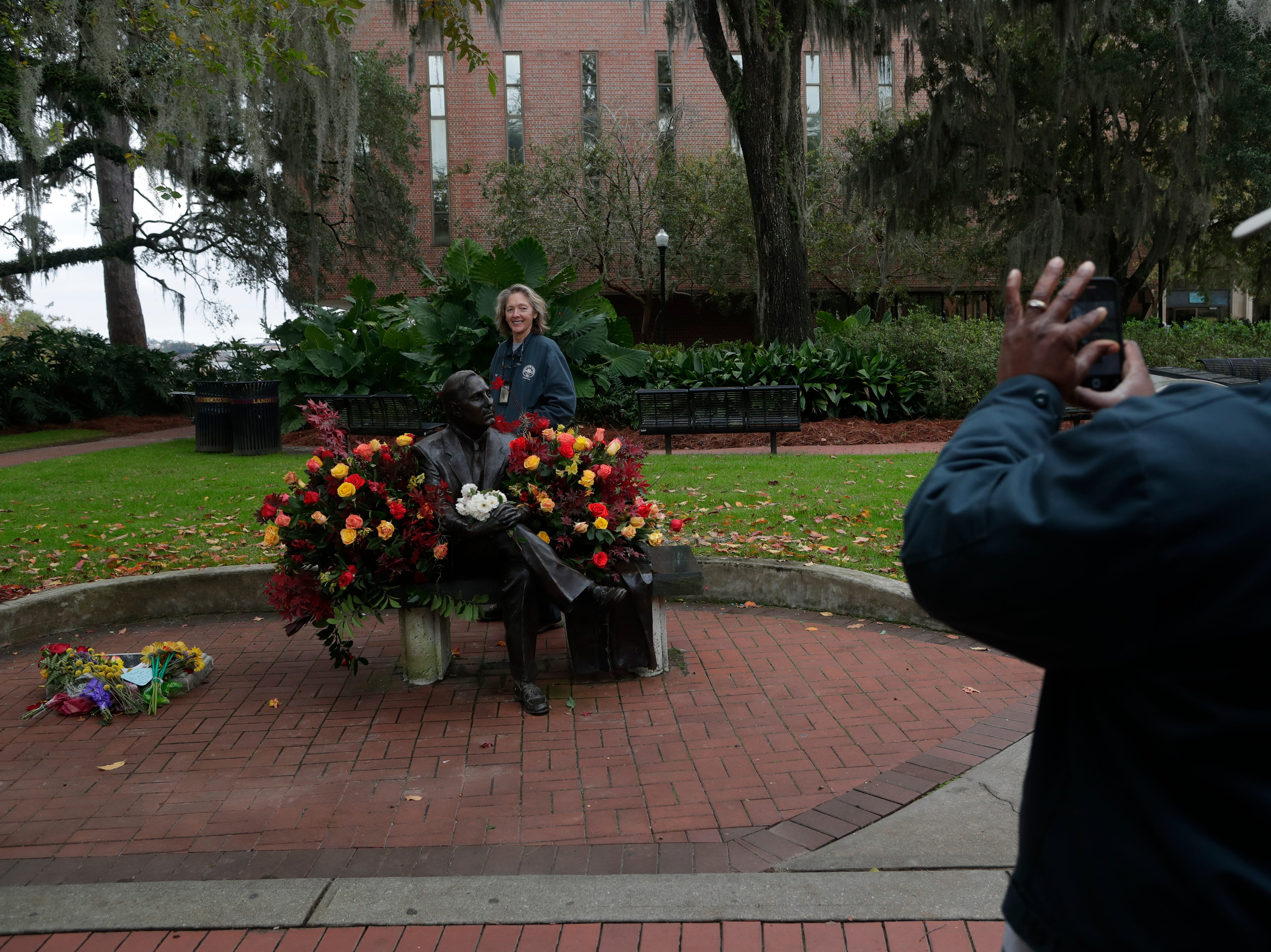 Florida State University Grounds Department employeee Betsy Smith gets her photo taken by her colleague Kenneth Prather before a funeral service for Florida State University President Emeritus T.K. Wetherell held at Ruby Diamond Concert Hall Friday, Dec. 21, 2018.