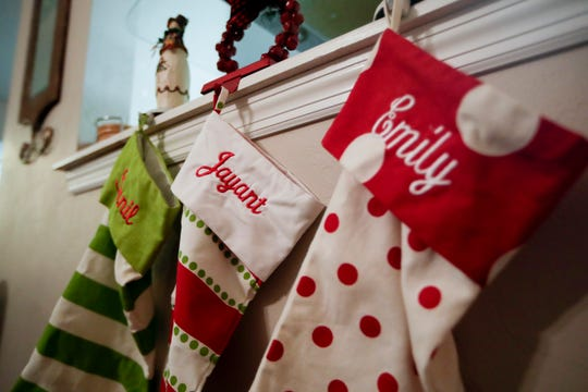 Three stockings hang with the name of all three of the Karnik family members as they get ready to celebrate the holidays.