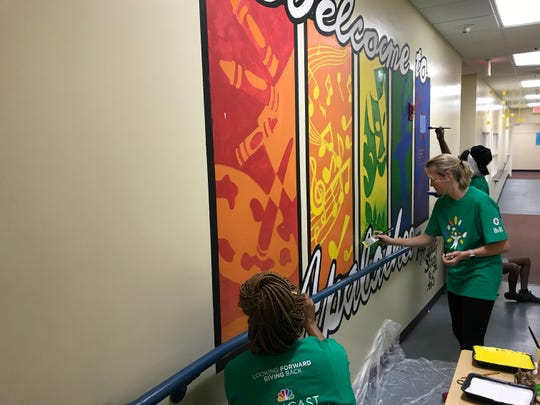 Volunteers at Apalachee Tapestry Magnet School of the Arts paint a mural during Comcast Cares Day on April 21, 2018.