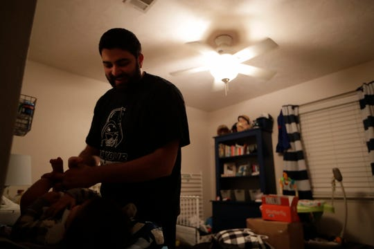 Sunil Karnik changes Jayant Karnik's diaper in his room at the home of Sunil's mother where the family lives Thursday, Dec. 6, 2018. Because of Jayant's spina bifida, he requires that his diaper be changed very regularly, sometimes more than once in an hour span.
