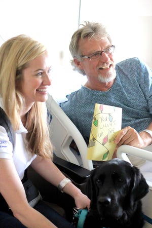 Animal Therapy dog  Brody and Margot distributing care cards with patients  in the Tallahassee Memorial Orthopedic Center.