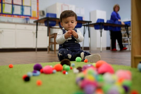 Jayant Karnik plays with fuzzy balls and other sensory items during an occupational therapy session with Premiere Therapy at his day care Wednesday, Nov. 28, 2018.