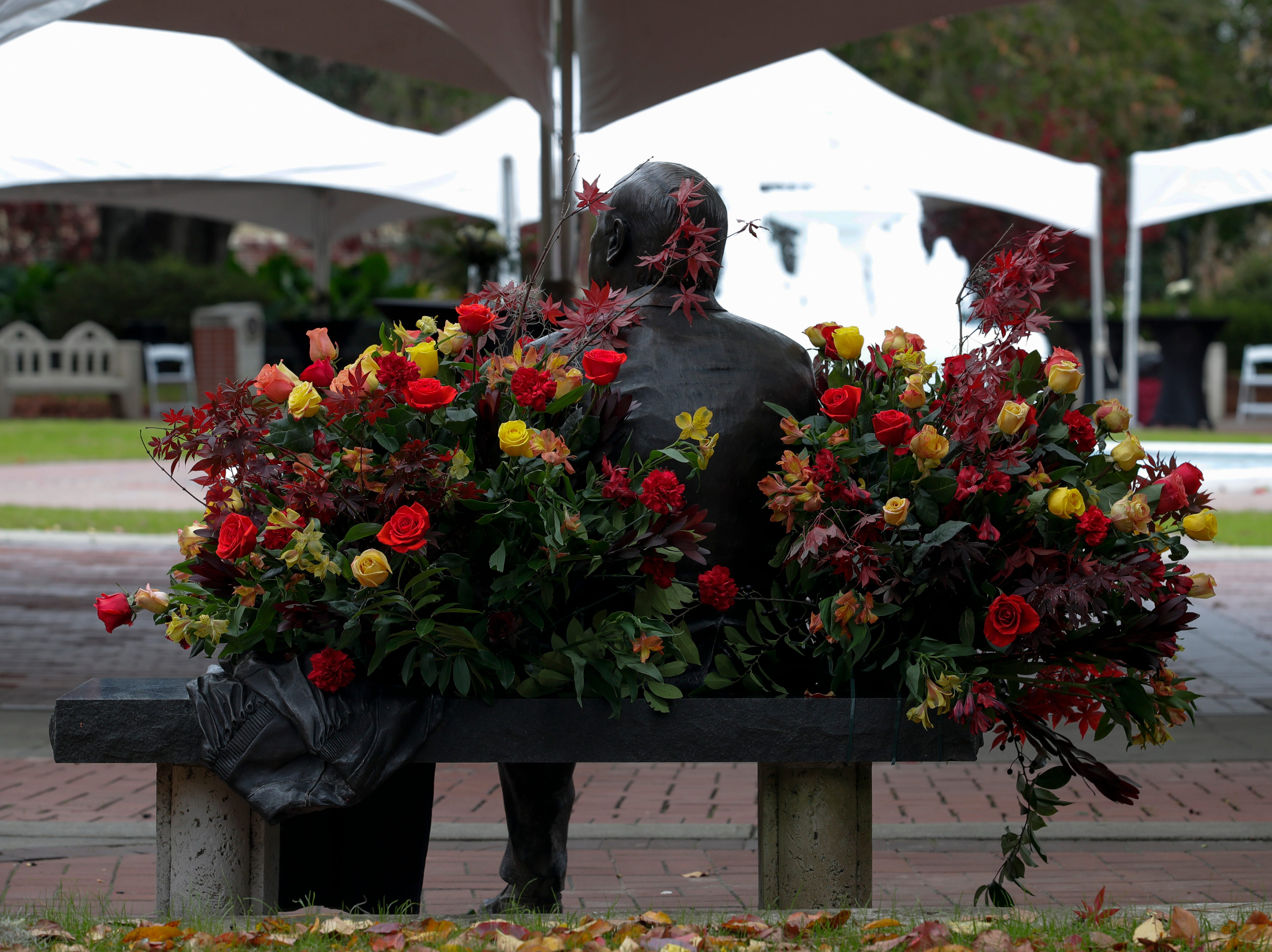 The statue of Florida State University President Emeritus T.K. Wetherell is covered in flowers just before his funeral service held at Ruby Diamond Concert Hall Friday, Dec. 21, 2018.