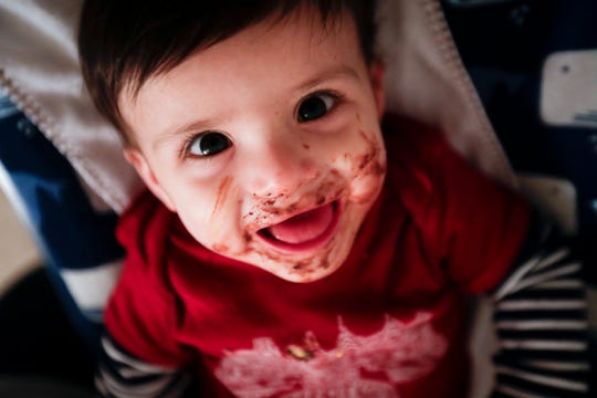 With cake smeared all over his face, Jayant Karnik smiles as his mom cleans up him after he ate his birthday cake at his first birthday party Sunday, Dec. 9, 2018.