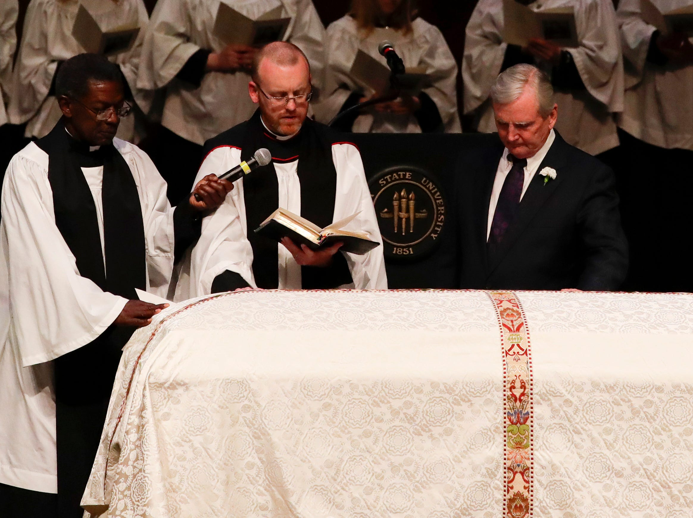 Rev. Joe Bakker, Rev. David Killeen and Bob Williamson pray over the casket of Florida State University President Emeritus T.K. Wetherell during his funeral service held at Ruby Diamond Concert Hall Friday, Dec. 21, 2018.