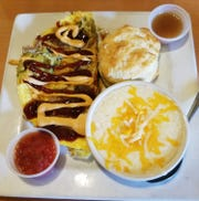 Berry Fresh Cafe's three egg Carnitas omelet with chipotle cream and barbecue sauce along with a side of fruit salsa. It was served with a side of slow cooked grits made with heavy cream and added cheddar cheese. The scratch-made biscuits had house made cinnamon apple butter.