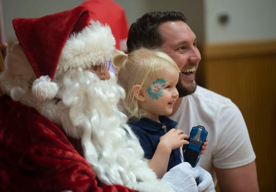 Pancakes with Santa is 10-11:30 a.m. Friday at the Port St. Lucie Community Center, 2195 S.E. Airoso Blvd. Last year, Harriet Clark, 2, along with her parents, Michael Clark (right) and Kate Clark (not pictured), took a photo with Santa.