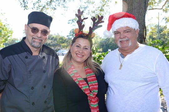 Paella King Chef Richard Blundell, left, with Diana and Tony Gonzalez of Ryde's Transport at the holiday party at Kids and Nurses PPEC in Vero Beach.