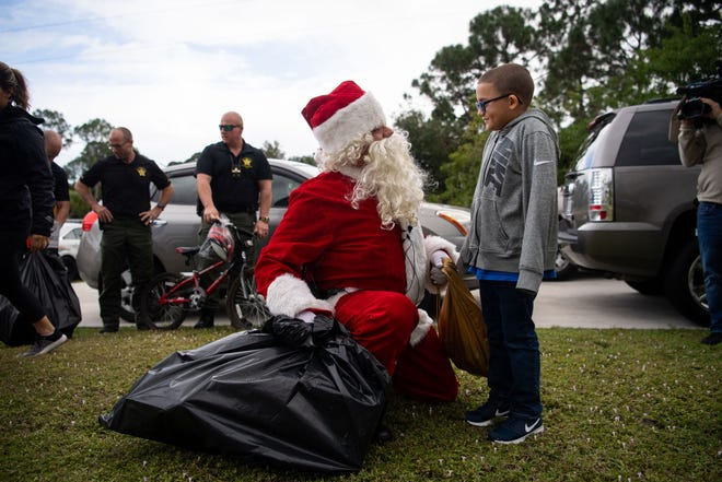 "Jamar Santiago Wise (right), 8, greets Santa Claus, who was escorted by the St. Lucie County Sheriff's Office, in front of the home he lives at with his grandmother, Elizabeth Bedolla, on Friday, Dec. 21, 2018, in Port St. Lucie. Jamar's mother, Tania Wise, was pregnant when she was found murdered in September in northwestern St. Lucie County. ""This is beautiful, and I want to thank everybody,"" Bedolla said. ""It's hard on him not having his mom."""