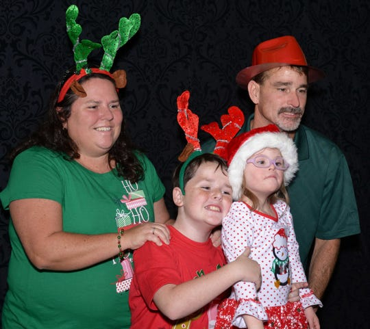 Melissa and Lance Argraves with children Logan and Lainey at a holiday party for Little Treasures patients at Treasure Coast Hospice's Fort Pierce office.