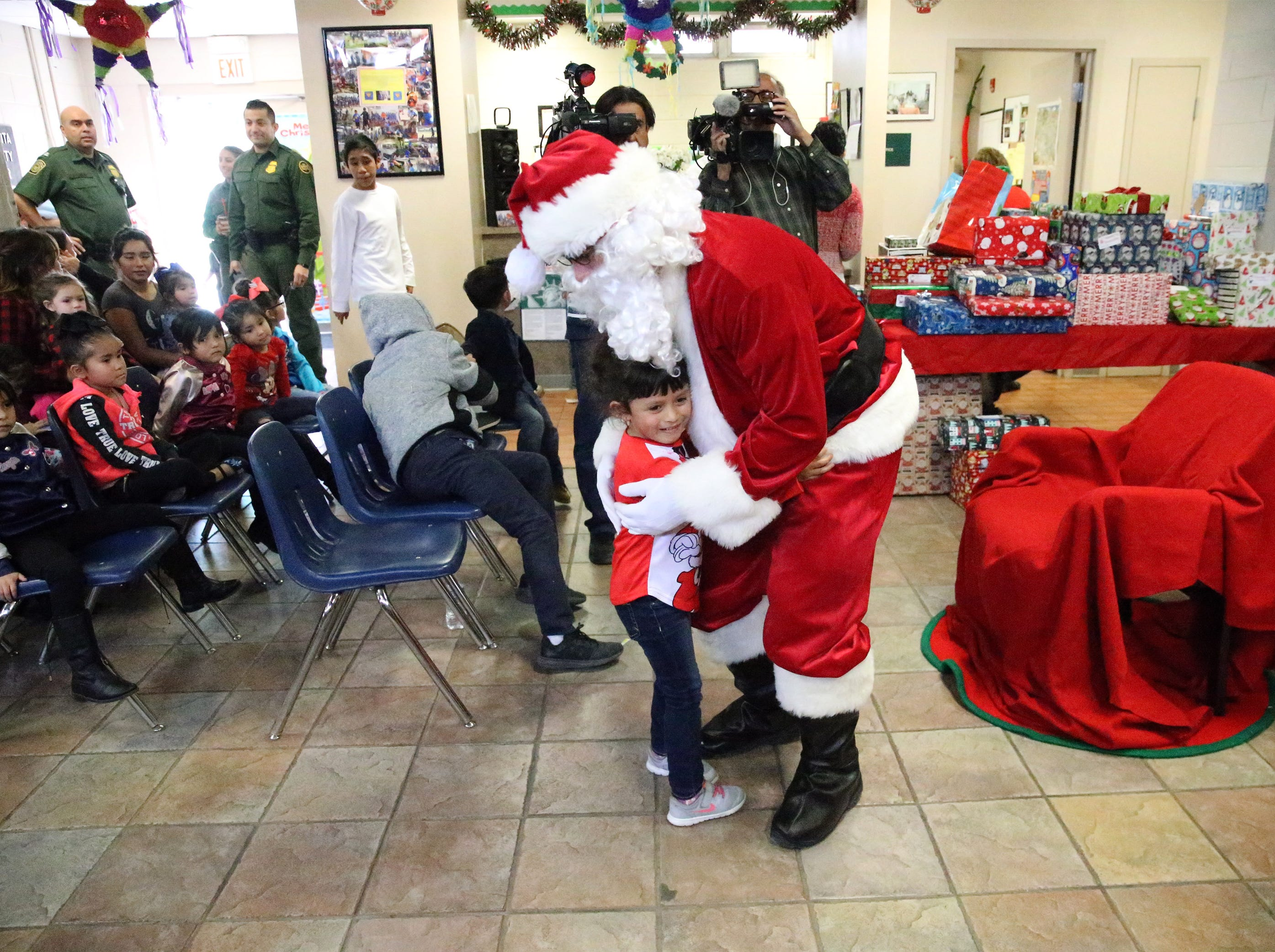 Children run up to greet Santa Clause upon his arrival at the Chihuahuita Community Center Friday.
