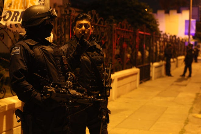 In the July 2010 file photo, Mexican police officers stand guard during the height of the cartel drug war in Juarez.