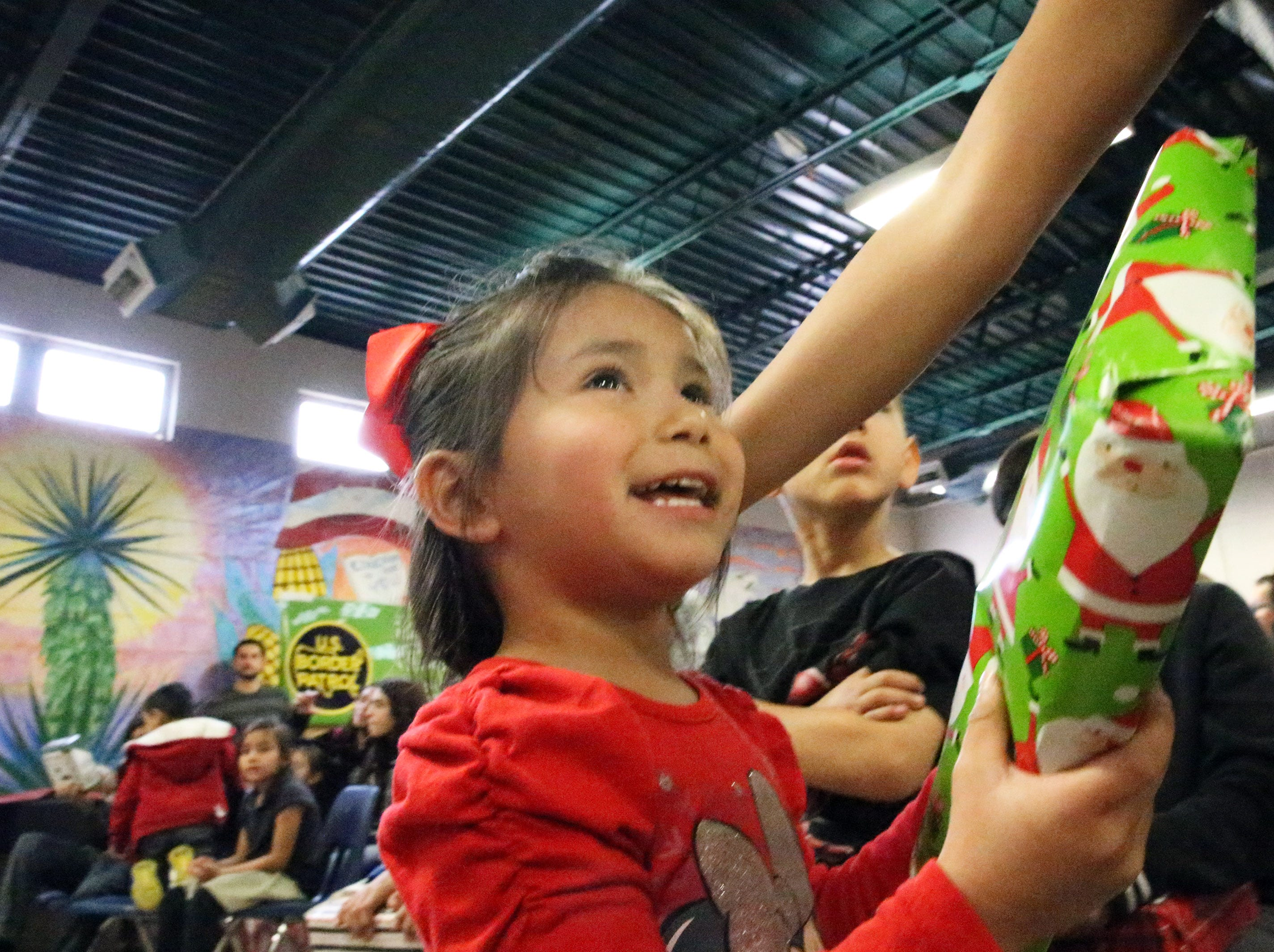 Mia Rojas, 3, beams after receiving her gift from Santa Clause Friday.