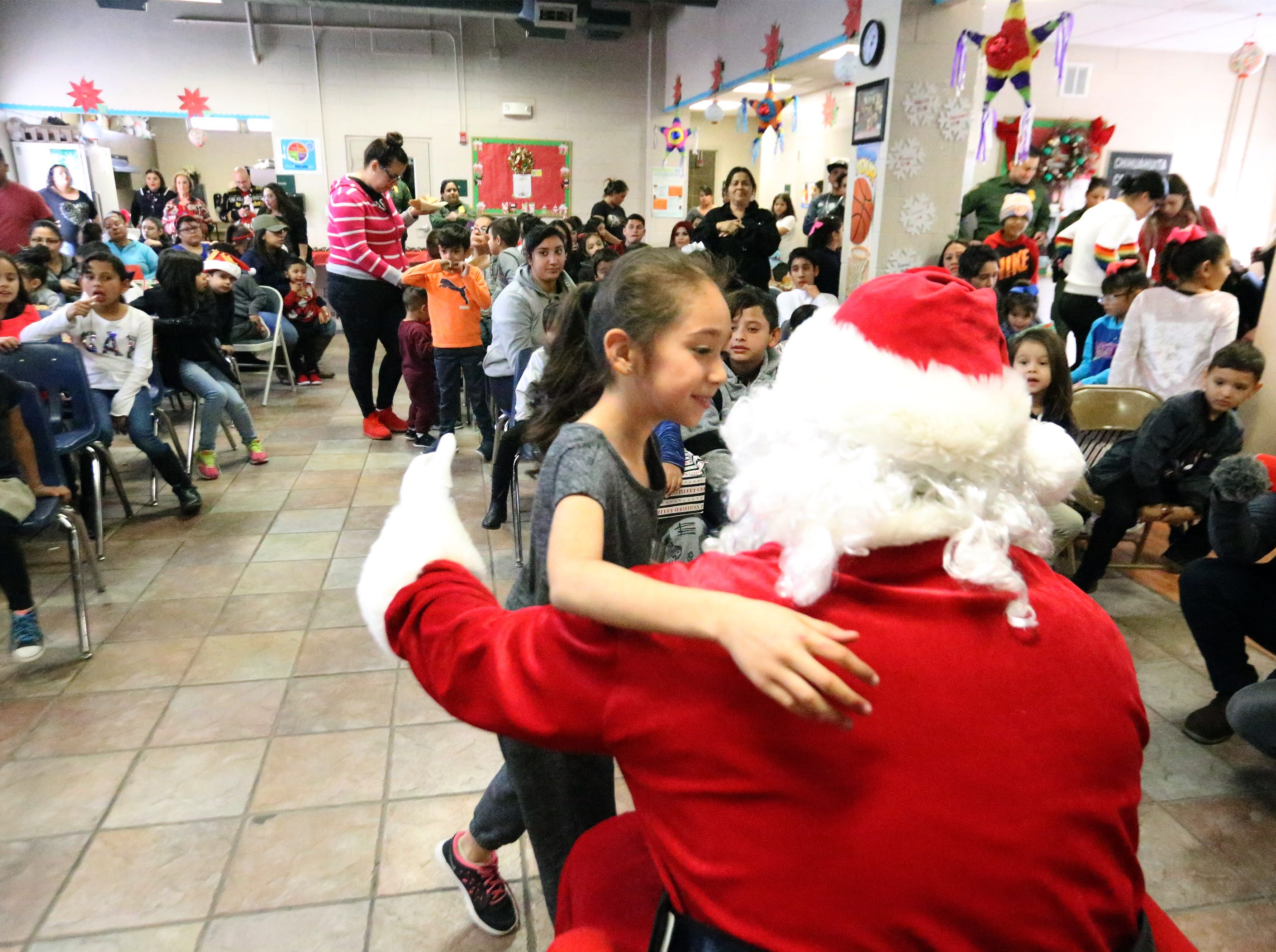 Santa gets a hug during the 26th U.S. Border Patrol Christmas Party Friday in the Chihuahuita community.