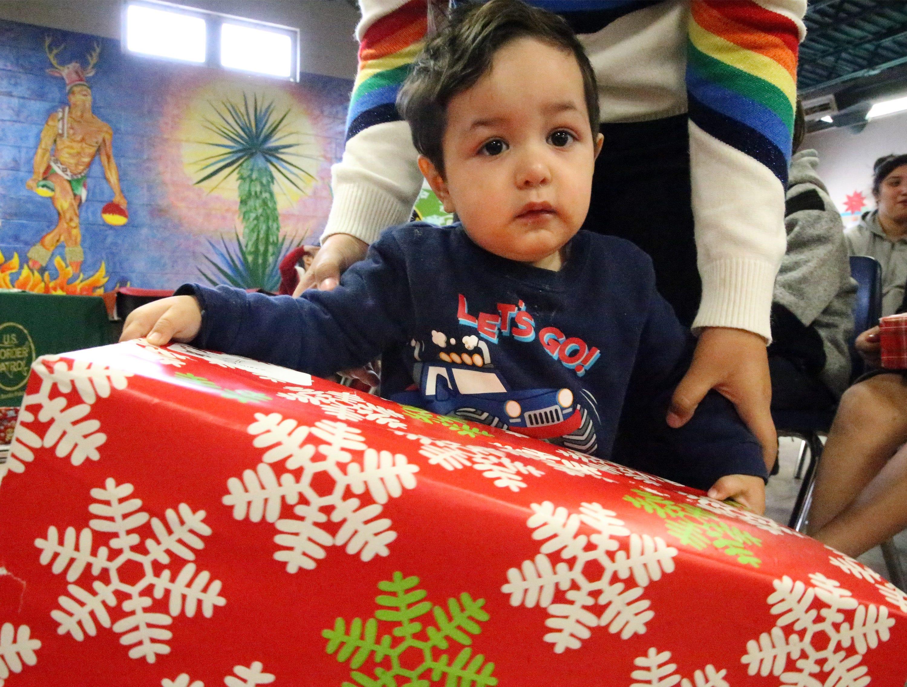 Eli Ramirez is helped with his Christmas gift Friday.