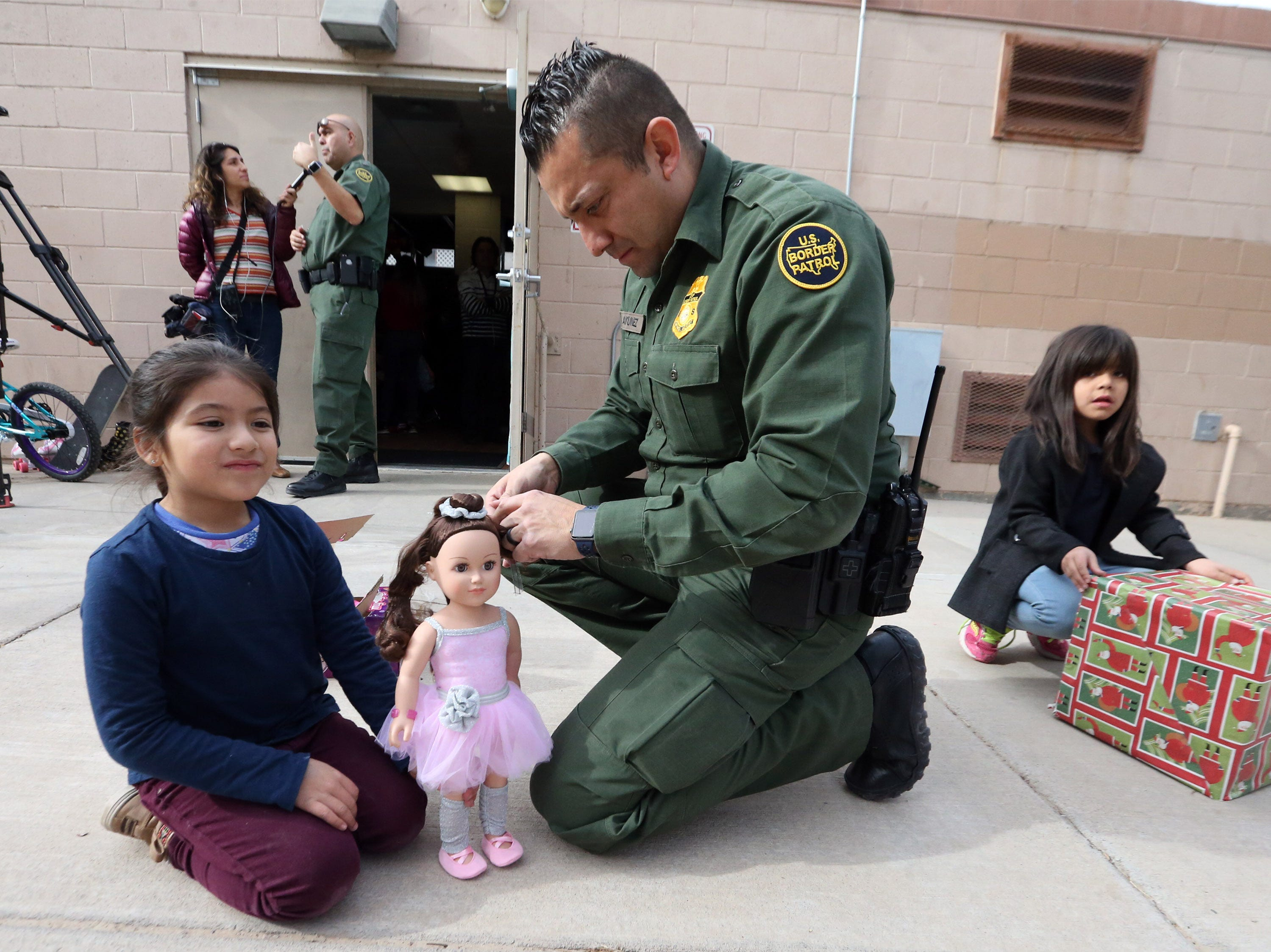 U.S. Border Patrol agent Carlos Antunez helps Ximena Cibrian unwrap her gift outside the Chihuahuita Community Center Friday.