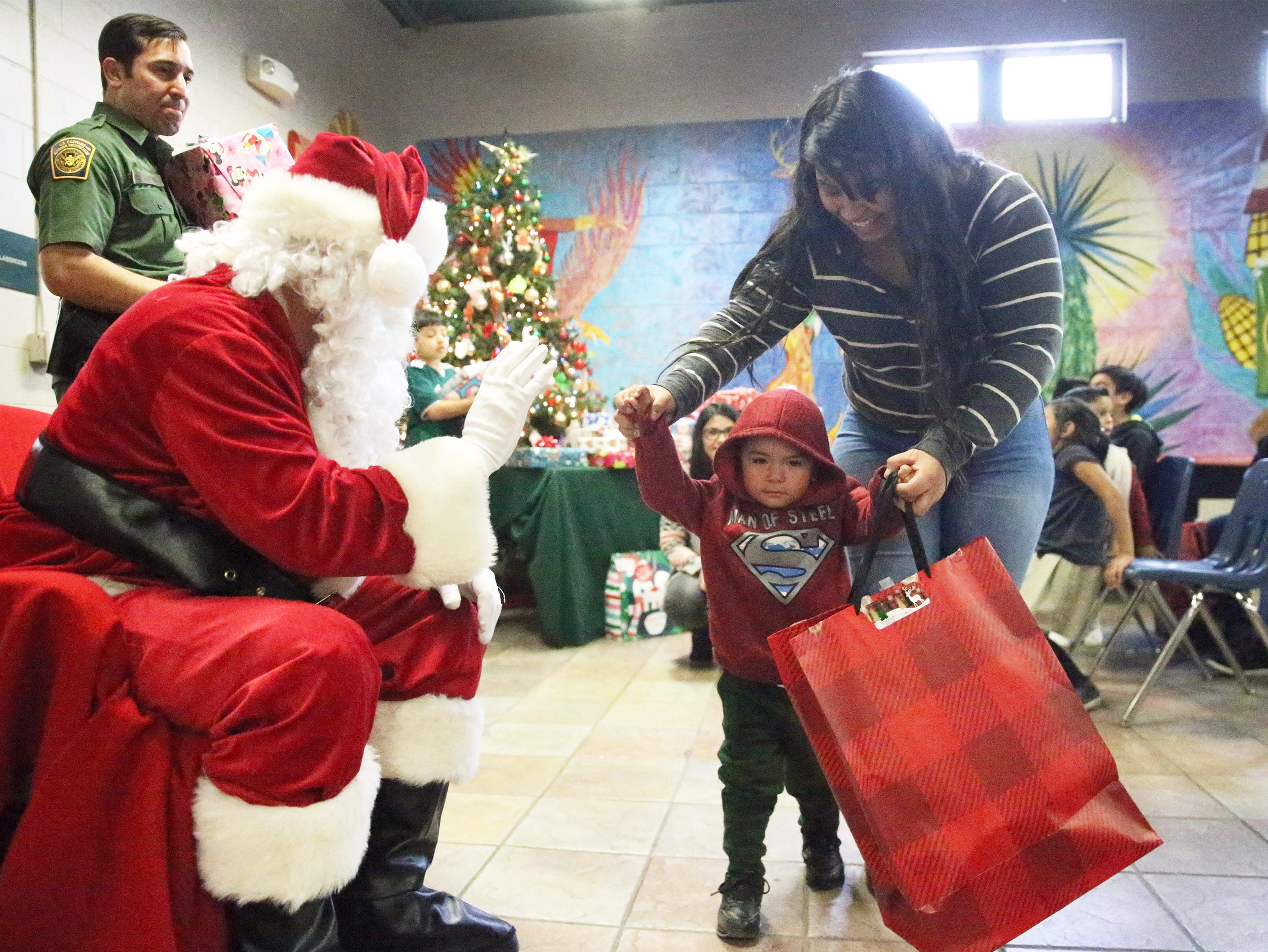 Young Fernando Uranga is helped with his gift from Santa Clause during the 26th U.S. Border Patrol Chihuahuita Christmas Party Friday at the Chihuahuita Community Center.