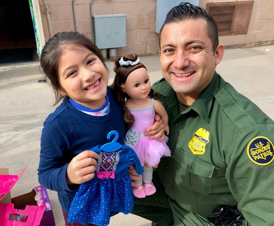 Ximena Cibrian, 5, gets help unwrapping her doll from U.S Border Patrol agent Carlos Antunez  onFriday at the Chihuahuita Community Center.