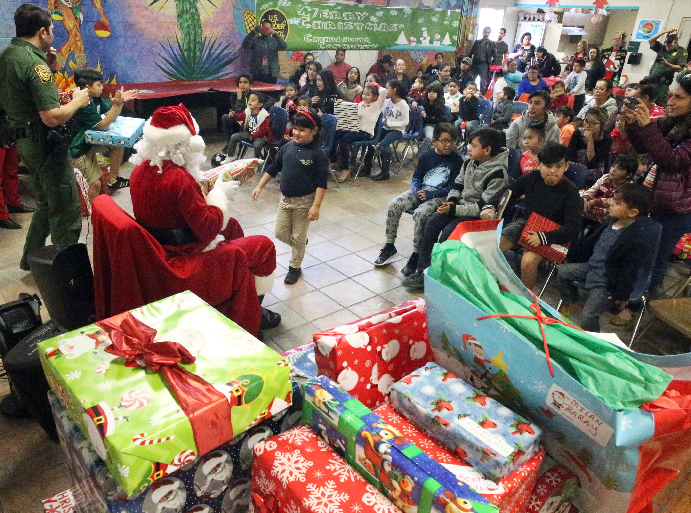 """Santa Clause hands out gifts to more than 100 youngsters during the 26th annual U.S. Border Patrol Chihuahuita Christmas Party Friday at the Chihuahuita Community Center at 417 Charles Road. """"Its one of the things Border Patrol likes to do for the community,"""" said spokesman Carlos Antunez, adding that the children from the neighborhood see them every day. Santa rode up in back of a pickup truck as children waited for him to arrive outside the community center. They were treated to holiday-themed snacks."""