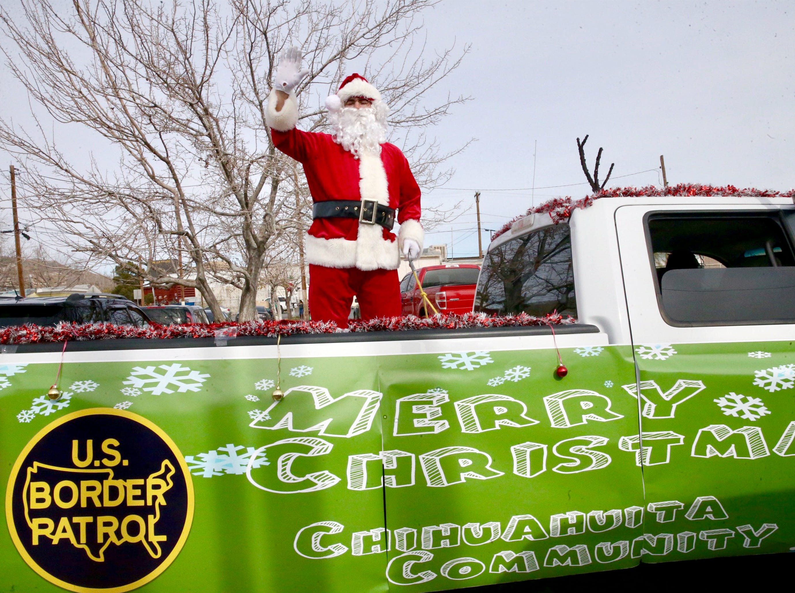 Santa arrives at the Chihuahuita Community Center on the back of a pickup truck Friday.