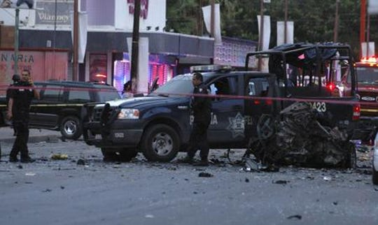 In this July 15, 2010, file photo, Mexican federal police agents secure the area after members of a drug gang rammed a car into two police patrol vehicles in retaliation for the arrest of a top gang leader in the northern border city of Juarez, Mexico. Two officers and an emergency medical technician were killed and a cameraman at the scene was injured; 2010 was the height of a Mexican cartel war in Juarez.