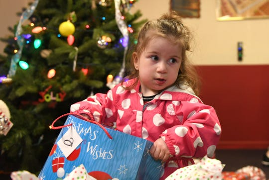 Addilynn Hines, 2, holds a gift bag at the Salvation Army in Vineland on Friday, December 21, 2018.