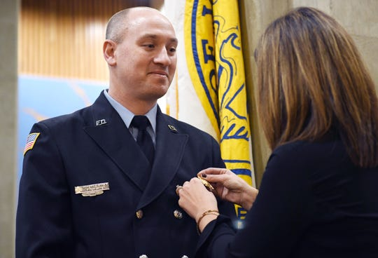 Dina Strain pins a lieutenant badge on her husband, Vineland firefighter Robert Strain, following a swearing in ceremony at City Hall on Friday, December 21, 2018.for the event.