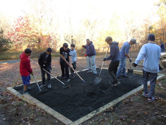 Kyle Bruenn (third from right, with shovel) working on a tent pad at Ward Pound Ridge Reservation in Cross River.