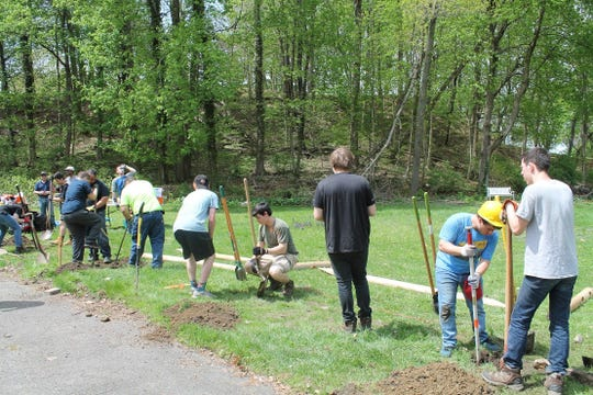 Joseph Dapice (second from right, wearing hard hat) digging a fence post for his Eagle Scout project at American Legion Post 1038 in Valhalla.