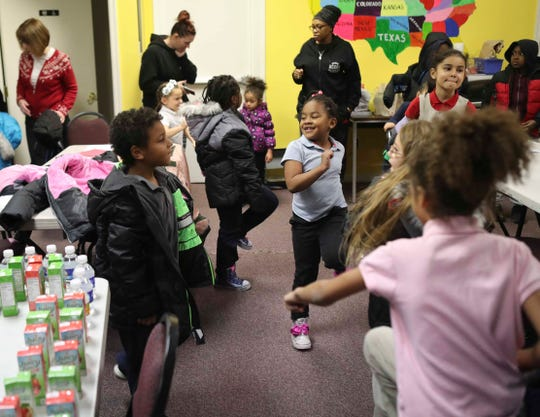 Children get some exercise in at a holiday party where the kids got coats and toys and the parents got Narcan at the Knollwood Community Center, where a health initiative included offering the opioid overdose treatment for nearby residents to have available in case of emergency.