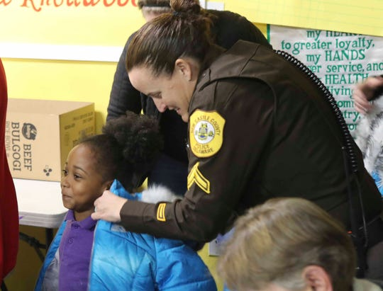 New Castle County Police OFC Colleen Kearns helps with coat giveaways to children at the Knollwood Community Center, where a health initiative included offering the opioid overdose treatment Narcan for nearby adult residents to have available in case of emergency.