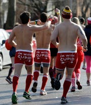 Three men run the 1-mile course during a Cupid's Undie Run in Cleveland.