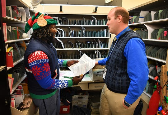 Postal carrier Joe Forbins, left, talks with Bridge Creek Station manager James Siegel while sorting mail for his route Friday morning. Forbins gets into the holiday spirit on December first with Christmas sweaters, candy and an elf hat.