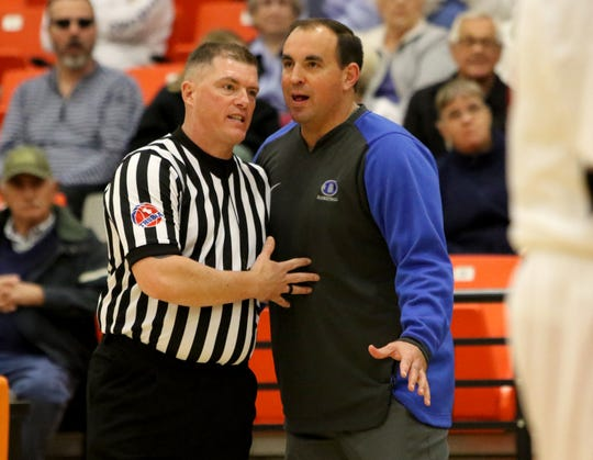 Decatur basketball coach Drew Coffman talks with an official about a foul during the Eagles' non-district game against Burkburnett earlier this season.
