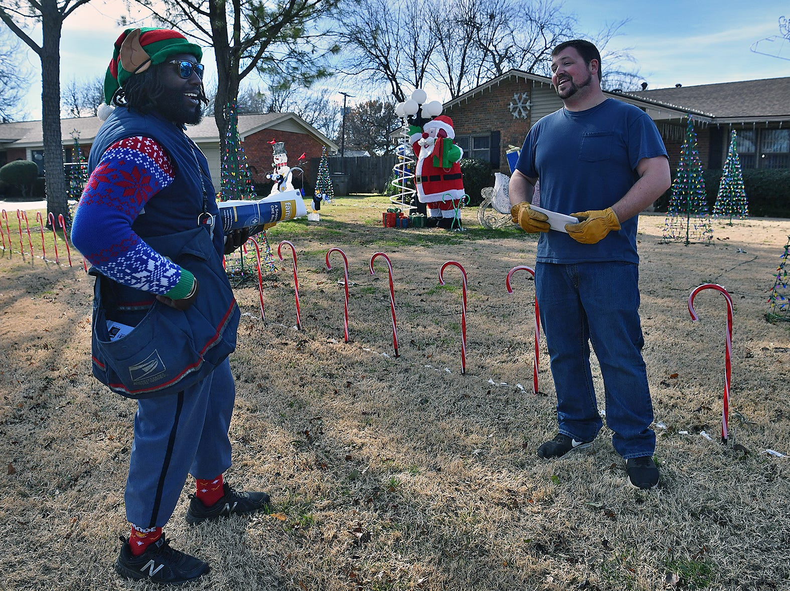 Postal carrier Joe Forbins talks with customer Jessie Elliott Friday afternoon. Forbins likes to spread cheer with fun hats, Christmas sweaters and a positive atitude.