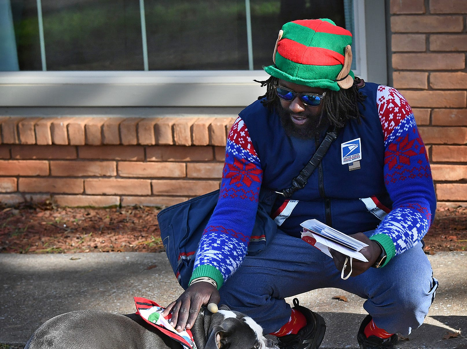 Joe Forbins, a mail carrier, stops to pet a dog on his route in the southwest part of town. In December, Forbins dons festive socks, hats and more to spread cheer during the workday.